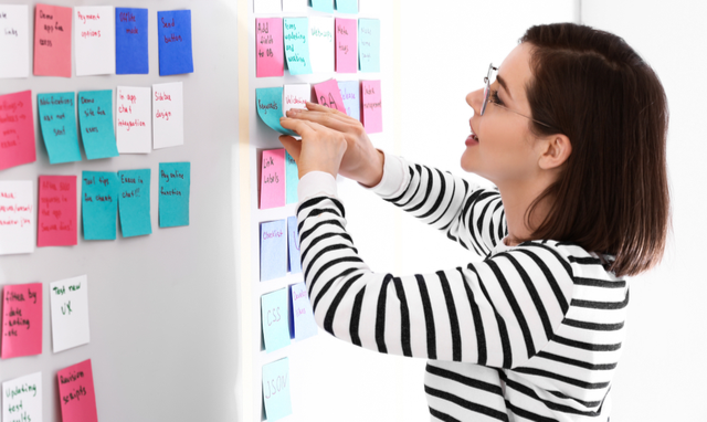 Woman building sticky note board for ideas and designs.
